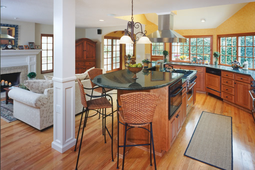 Kitchen Cabinets with Alder Wood Stained Angled Cabinets Raised Panel Doors Two-tiered Island