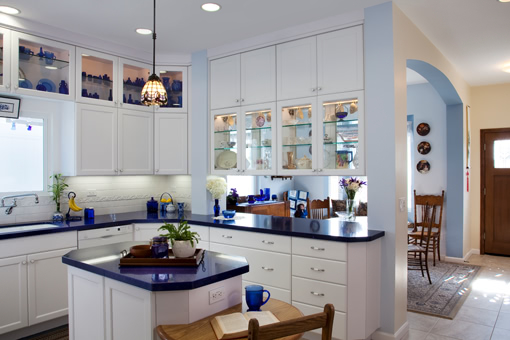 White Painted Kitchen Cabinets Recessed Panel Doors Solid Drawer Fronts Glass Doors on Upper Island with Lower Seating Area Pass-thru at Peninsula